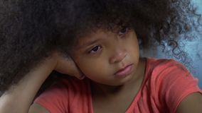 Trauriges gelocktes weibliches afro-amerikanisches Kind, das allein, bestraft für schlechtes Verhalten sitzt lizenzfreie stockfotos