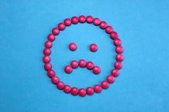 Trauriges Gesicht ausgebreitet von den rosa Pillen auf blauem Hintergrund stockfotos