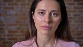 Trauriges Gesicht der kaukasischen Frau Kameranahaufnahme betrachtend und bei der Stellung der nahen Wand des roten Backsteins ni stock video