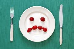Trauriges Gesicht gebildet von den Erdbeeren Stockfotos