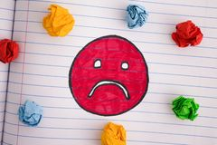 Trauriges Gesicht mit bunten zerknitterten Papierbällen auf Notizbuchblatt lizenzfreie stockfotos