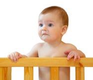 Trauriges halb-Jahr-altes Baby, welches das Seitenfeldbett hält Stockfoto