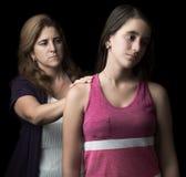Trauriges jugendlich Mädchen mit ihrer Angebothilfe der Mutter Stockbilder