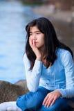 Trauriges jugendlich Mädchen, das auf Felsen entlang Seeufer, einsamer Ausdruck sitzt Lizenzfreie Stockfotos