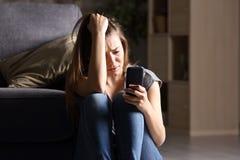 Trauriges jugendlich Prüfungstelefon zu Hause lizenzfreie stockbilder