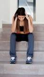 Trauriges Jugendlichmädchen, das auf der Treppe sitzt Stockfoto