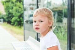Trauriges kaukasisches blondes Baby wartet auf eine Bank Stockfotografie