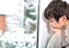 Trauriges Kind auf Fenster kann nicht erlöschen Stockbild
