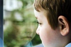 Trauriges Kind, das heraus Fenster schaut Lizenzfreie Stockfotos