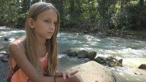 Trauriges Kind durch Fluss, durchdachtes Kind, das in der Natur, Mädchen beim Kampieren, Berg sich entspannt lizenzfreie stockfotos