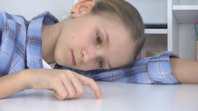Trauriges Kind, gebohrtes Mädchen, das Finger auf Schreibtisch, betontes unglückliches nicht studierendes Kind spielt stockfotografie