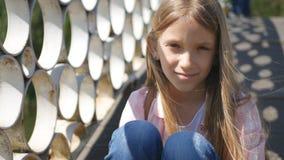 Trauriges Kind im Park, unglückliches durchdachtes Mädchen im Freien, gebohrtes nachdenkliches Kind auf Brücke lizenzfreie stockfotos