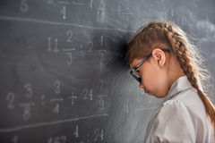 Trauriges Kind nahe der Tafel Stockfotos