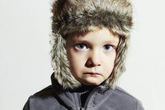 Trauriges Kind in Pelz Hut Scherzt zufällige Winterart Little Boy Kindergefühl Stockfoto