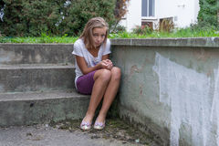 Trauriges Kind sitzt auf der einsamen Treppe Lizenzfreie Stockbilder