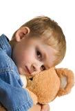 Trauriges Kind umfaßt einen Teddybären Stockbild