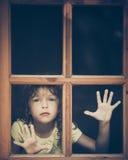 Trauriges Kind, welches heraus das Fenster schaut Stockbild