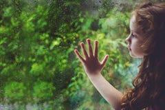 Trauriges Kind, welches heraus das Fenster schaut Stockbilder