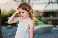 Trauriges Kindermädchen mit Kopfschmerzen auf Sommerspielplatz lizenzfreie stockfotografie
