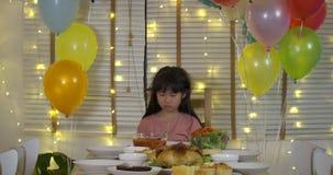 Trauriges kleines asiatisches Mädchen, das ihren Geburtstag allein an einem Tisch mit einem Kuchen und an einer Kerze in der Zeit stock footage
