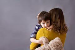 Trauriges kleines Kind, Junge, seine Mutter zu Hause umarmend Stockfoto