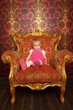 Trauriges kleines Mädchen, das im alten Lehnsessel sitzt Stockfoto