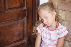 Trauriges kleines Mädchen, das nahe einer Tür sitzt Stockfotos