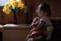 Trauriges kleines Mädchen, das Teddybären umarmt Stockfoto