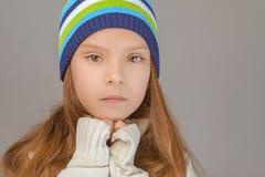 Trauriges kleines Mädchen in der Strickmütze lizenzfreie stockfotos