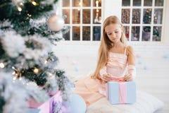 Trauriges kleines Mädchen in einem eleganten rosa Kleid, das Geschenkbox nahe Weihnachtsbaum hält Stockfoto