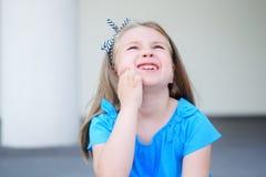 Trauriges kleines Mädchen mit dem langen blonden Haar, das unter Zahnschmerzen leidet Lizenzfreies Stockfoto