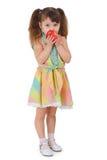 Trauriges kleines Mädchen, zum des Apfels auf weißem Hintergrund zu essen Lizenzfreies Stockfoto