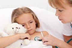 Trauriges kleines Mädchen, das Kranken im Bett legt Lizenzfreie Stockfotografie
