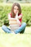 Trauriges Kursteilnehmermädchen, das nahe Stapel der Bücher sitzt Stockbild