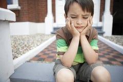 Trauriges Little Boy, das auf Front Steps sitzt Lizenzfreie Stockfotografie