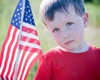 Trauriges Little Boy mit amerikanischer Flagge Stockfoto