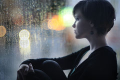 Trauriges Mädchen auf dem Fensterbrett, welches heraus das Fenster schaut Stockfotos
