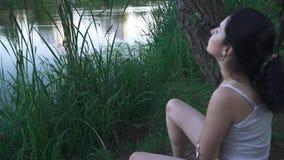 Trauriges Mädchen auf der Flussbank stock video