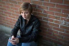 Trauriges Mädchen, das außerhalb der Backsteinmauer in der Schule yar sitzt Lizenzfreie Stockbilder