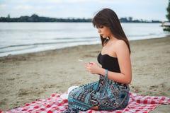 Trauriges Mädchen, das auf dem Strand sitzt und das Telefon betrachtet Lizenzfreie Stockbilder