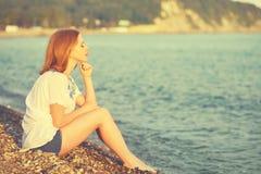 Trauriges Mädchen, das auf dem Strand und den Blicken in den Abstand in Meer sitzt Stockfotografie