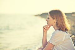 Trauriges Mädchen, das auf dem Strand und den Blicken in den Abstand an Se sitzt Lizenzfreies Stockbild