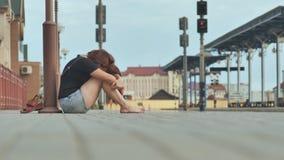 Trauriges Mädchen, das auf den Fliesen des Bahnhofs in den Kopfhörern und im Schreien sitzt stock video