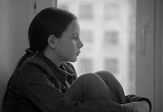 Trauriges Mädchen, das auf einem Fensterbrett in der Krise sitzt lizenzfreie stockfotografie