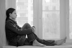 Trauriges Mädchen, das auf einem Fensterbrett in der Krise sitzt lizenzfreies stockbild