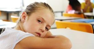 Trauriges Mädchen, das auf Schreibtisch in der Klasse liegt stock video