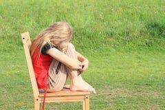 Trauriges Mädchen, das auf Stuhl sitzt Lizenzfreie Stockbilder