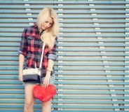 Trauriges Mädchen, das ein rotes Herz und Stände nahe einer Wand von farbigen hölzernen Planken hält Stockfotografie