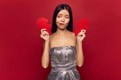Trauriges Mädchen, das großes defektes rotes Herz hält Valentinstag und Liebeskonzept, Scheidung allein einzeln lizenzfreies stockbild