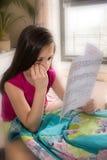 Trauriges Mädchen, das ihr Schulzeugnis betrachtet Lizenzfreie Stockfotos